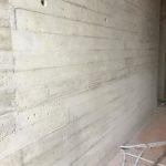 Weggewerkte grindnesten in een betonwand met plankenstructuur